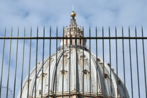 "A picture shows the cuppola of St Peter's basilica behind a fence on March 14, 2016 in Vatican during the ""Vatileaks"" trial of two journalists and three former Vatican officials.  A controversial Vatican trial of journalists and alleged whistleblowers resumes today, in the latest instalment of an image-bruising legal saga. The spicy courtroom drama has already served up claims of sexually charged scheming, blackmail and computer hacking behind the fortified walls of the secretive city state.  / AFP / ALBERTO PIZZOLI"