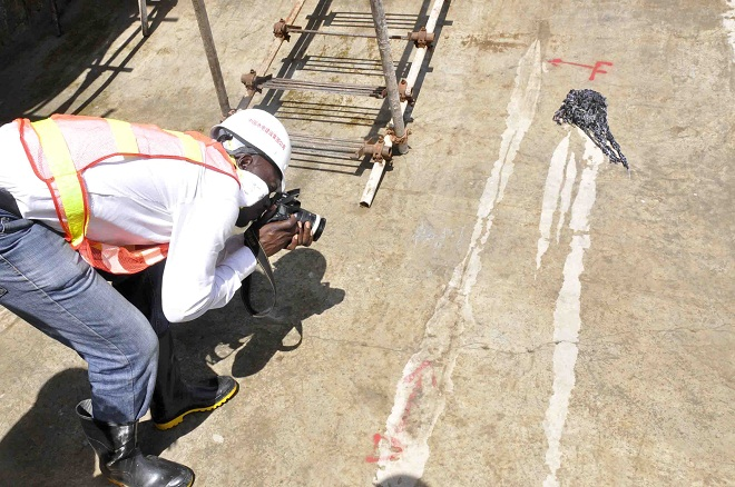 A journalist trying to take a picture of the cracked Karuma bridge sluice gates.