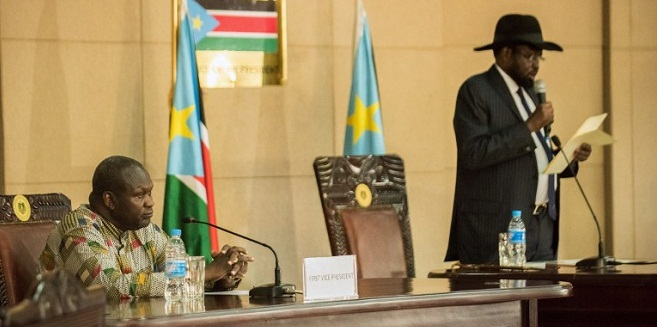 President Salva Kiir (R) delivers a statement as former rebel leader and new vice-president Riek Machar listens during a ceremony at the Presidential House in Juba after Machar was sworn in as new vice-president, following hus arrival at Juba international airport on April 26, 2016. The return of rebel leader Riek Machar to Juba must pave the way for a genuine transition to end more than two years of brutal civil war in South Sudan, the UN peacekeeping chief said on April 26.  / AFP PHOTO / Charles Lomodong