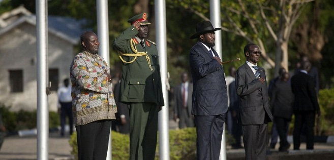 Former rebel leader and new vice-president Riek Machar (Rear C) and President Salva Kiir (2nd R) listen to the national anthem at the Presidential House in Juba after Machar was sworn in as new vice-president, after Machar landed at Juba international airport on April 26, 2016. The return of rebel leader Riek Machar to Juba must pave the way for a genuine transition to end more than two years of brutal civil war in South Sudan, the UN peacekeeping chief said on April 26. / AFP PHOTO / Albert Gonzalez Farran
