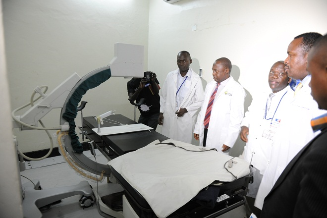 Minister Elioda Tumwesigye shows journalists a brachytherapy machine at the radiology unit. unlike the Cobalt machine, this provides internal radiation.