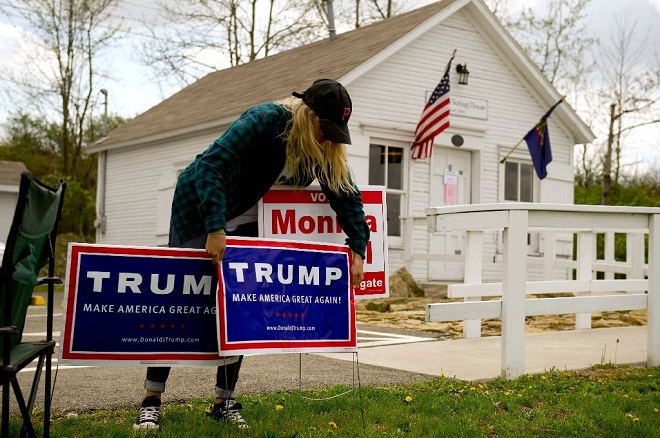 A woman places a Trump sign outside the Simpson Voting House, built in 1891, on April 26, 2016 in New Alexandria. AFP PHOTO