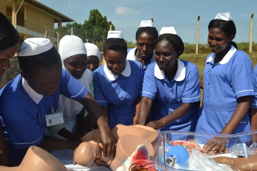 Trainee midwives demonstrating the childbirth process using a birth simulator in Kampala, Uganda. PHOTO UN