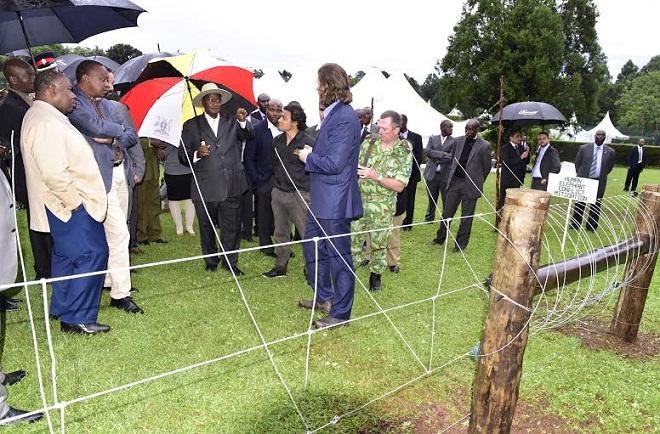 Museveni, Kenyatta and Bongo being shown an electric fence used to control movement of elephants.
