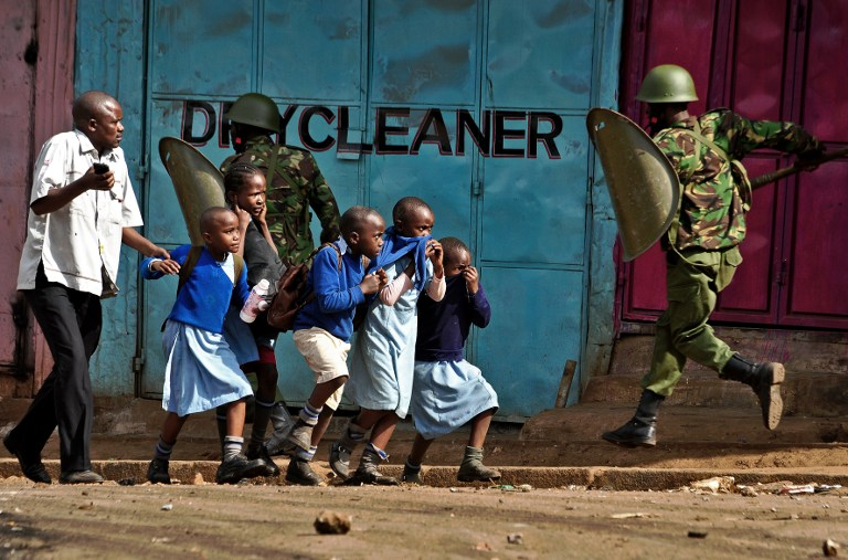 Riot policemen run past school children during a demonstration of opposition supporters protesting for a change of leadership at the electoral commission ahead of a vote due next year, in Kibera slum, Nairobi on May 23, 2016. Local media reported at least one killed in Kisumu in the west of the country, while police in Nairobi and the second city of Mombasa fought running battles with small groups of protesters.There was no immediate police confirmation of the reported death. Police had banned the planned demonstrations and scores of officers in riot gear guarded the building that houses the election commission headquarters in the centre of the capital. / AFP PHOTO / KEVIN MIDIGO