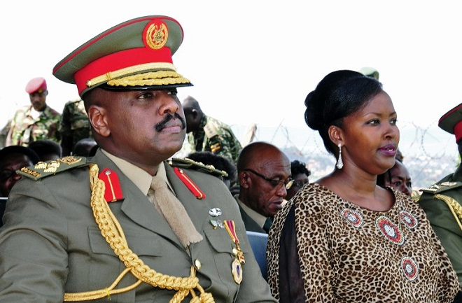 The son of Uganda's President Yoweri Museveni, Major General Muhoozi Kainerugaba (L) and his wife Charlotte Kutesa Kainerugaba (R) attend a ceremony in which Kainerugaba is promoted from Brigadier to Major General at the country's military headquarters . AFP PHOTO