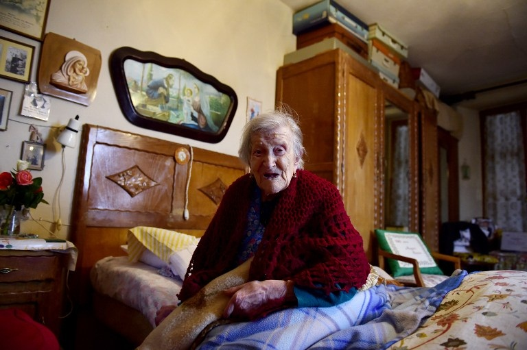 """Emma Morano, 116, holds a pillow reading """"116 years old, Happy Birthday Emma"""" as she poses for AFP photographer in Verbania, North Italy, on May 14, 2016.   Emma Morano is the oldest living person in the world, and the only one left who has touched three centuries. Susannah Mushatt Jones, a New York woman several months her senior, died on May 12 evening, making Morano the world's oldest known person at 116. / AFP PHOTO"""