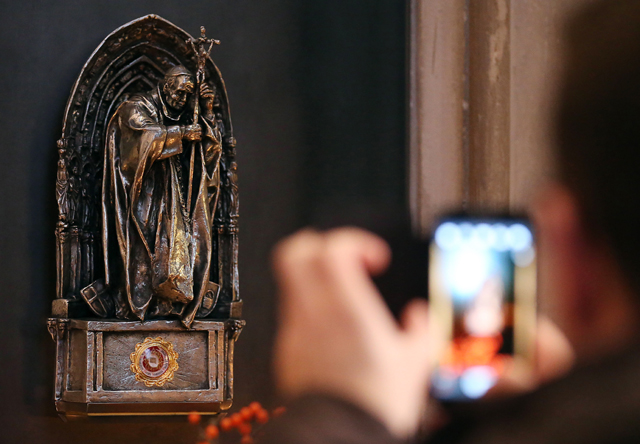 Picture taken on December 10, 2013 shows a tourist photographing a statue containing the relic of Pope John Paul II, in the Cologne cathedral, western Germany. A cloth with a drop of Pope John Paul II's blood was stolen from Cologne Cathedral in western Germany at from June 4 to 5, 2016 , police said. / AFP PHOTO / dpa / Oliver Berg / Germany OUT