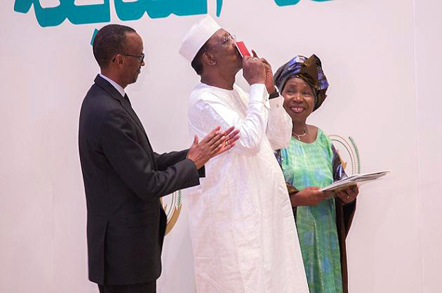 Rwanda President Paul Kagame applauds Chad President Idriss Deby Itno who kisses the African Passport.