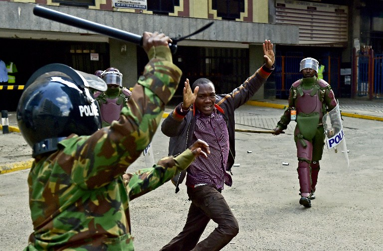 Kenyan riot police officers raise batons over a man during a demonstration of Kenya's opposition supporters in Nairobi, on May 16, 2016.  Opposition protestors led by former Prime Minister Raila Odinga gathered outside the Indepedent Electoral and Boundaries Comission building to demand the dismissal of IEBC commissioners, after alleged bias towards the ruling Jubillee Alliance Party. / AFP PHOTO / CARL DE SOUZA