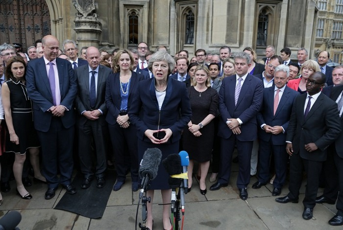 Britain's new Conservative Party leader Theresa May (C), flanked by her supporters, speaks to members of the media at The St Stephen's entrance to the Palace of Westminster in London on July 11, 2016. Theresa May will on Wednesday become the prime minister who leads Britain's into Brexit talks after her only rival in the race to succeed David Cameron pulled out unexpectedly. May was left as the only contender standing after the withdrawal from the leadership race of Andrea Leadsom, who faced criticism for suggesting she was more qualified to be premier because she had children. / AFP PHOTO / DANIEL LEAL-OLIVAS