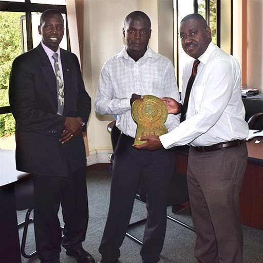 FILE PHOTO UWA: Ssegamwenge Henry Technical Director of Nile Comrades Group of Companies Hands over an UWA Logo Bronze Plaque to Dr. Andrew Seguya in presence of Mr. Stephen Masaba the UWA Business Development Manager