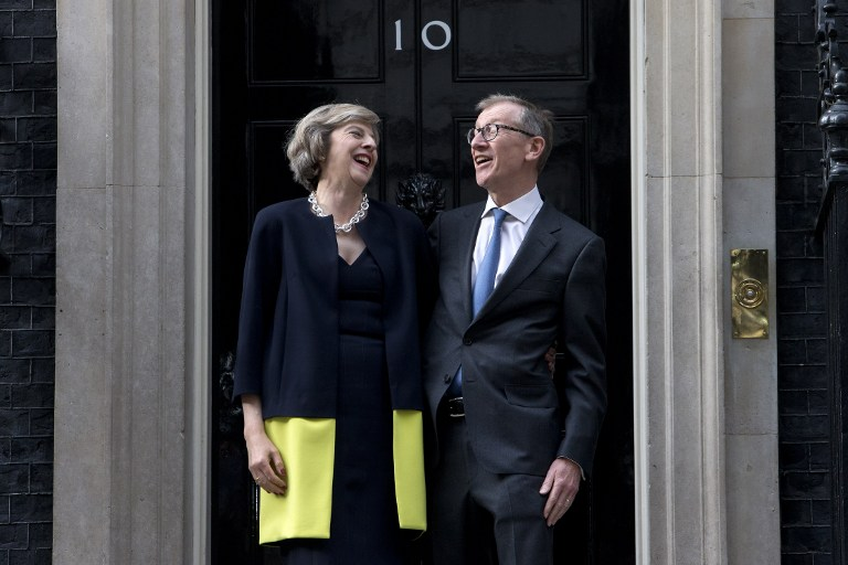 Britain's new Prime Minister Theresa May (L) and her husband Philip John May (R) laugh together outside the door of 10 Downing Street in central London on July 13, 2016 on the day that Theresa May takes office following the formal resignation of David Cameron.  Theresa May took office as Britain's second female prime minister on July 13 charged with guiding the UK out of the European Union after a deeply devisive referendum campaign ended with Britain voting to leave and David Cameron resigning.   / AFP PHOTO / JUSTIN TALLIS