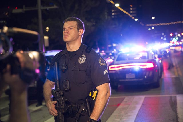 A Police officer stands guard at a baracade following the sniper shooting in Dallas on July 7, 2016. A fourth police officer was killed and two suspected snipers were in custody after a protest late Thursday against police brutality in Dallas, authorities said. One suspect had turned himself in and another who was in a shootout with SWAT officers was also in custody, the Dallas Police Department tweeted. / AFP PHOTO / Laura Buckman