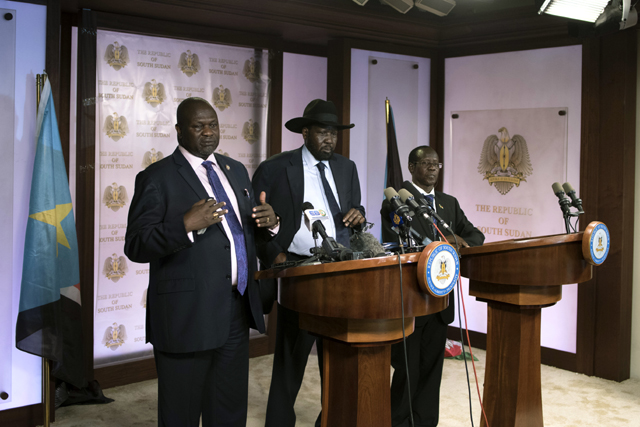 First Vice President Riek Machar (L) delivers a speech to journalists next to South Sudan President Salva Kiir (C) and Vice President James Wani Igga (R) prior to the shooting outside the presidential palace in Juba on July 8, 2016. Gunfire erupted near the presidential palace in South Sudan's capital Juba on July 8, further straining a shaky ceasefire the day after five soldiers were killed. / AFP PHOTO / Charles Atiki Lomodong