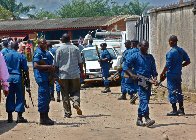 "Security personnel block the area close to where the body of Col. (Rtd) Lucien Rufyiri lies on May 25, 2015 in the Burundian capital, Bujumbura after he was gunned down by unidentified gunmen as he arrived at his residence. The Tutsi colonel who has been retired for several years was killed outside his home in a rebellious district of Bujumbura ""by armed criminals"", according to a source within the family. ""Colonel Lucien Rufyiri has been murdered this morning in front of his house and a son who was with him was injured,"" he told AFP a family member, who requested anonymity. / AFP PHOTO / ONESPHORE NIBIGIRA"