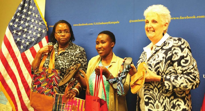 (L-R) Margaret Waithaka of the East Africa Trade and Investment Hub, Agnes Netunze of Sseko Designs, and the US Ambassador to Uganda, Deborah Malac dispalys some of the products (leather shoes and bags) that the design firm exports to the US markets under the African Growth and Opportunity Act(AGOA) at the US Embassy on August 10. Independent Photo/ISAAC KHISA