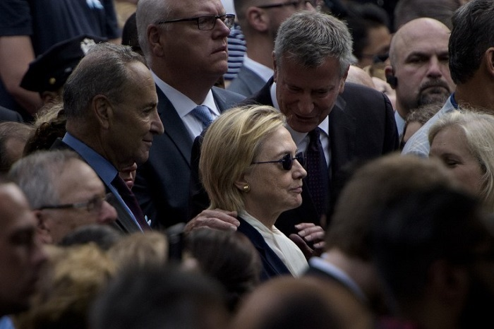 New York City Mayor Bill de Blasio speaks to US Democratic presidential nominee Hillary Clinton during a memorial service at the National 9/11 Memorial September 11, 2016 in New York. The United States on Sunday commemorated the 15th anniversary of the 9/11 attacks. / AFP PHOTO / Brendan Smialowski