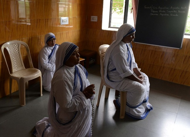 "In this photograph taken on August 28, 2016, Indian nuns pray at 'Shanti Nilaya', a home for the dying and destitute run by Mother Teresa's Missionaries of Charity in Ahmedabad. Known as the ""Angel of Mercy"" for serving the poor in India, Mother Teresa will be declared a saint on September 4, amid great fanfare. But as the Vatican prepares her canonisation, allegations of fraud and medical negligence cloud her legacy. / AFP PHOTO / SAM PANTHAKY"