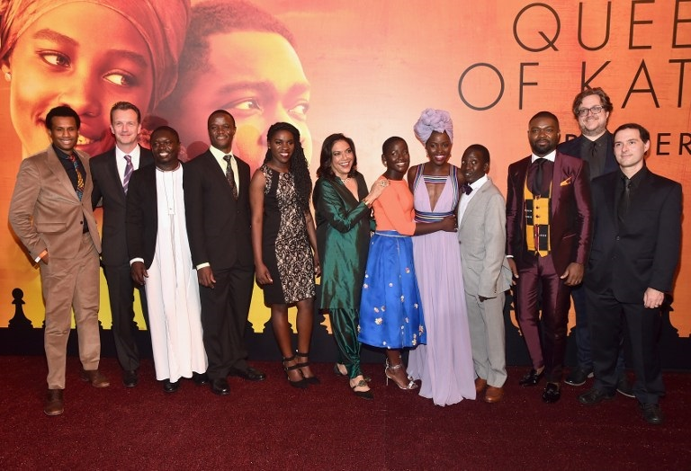 HOLLYWOOD, CA - SEPTEMBER 20: (L-R) Executive Vice President of Production, The Walt Disney Studios, Tendo Nagenda, President of Walt Disney Studios Motion Picture Production, Sean Bailey, chaperone Mark Mugwana, Chess Coach and Director of Sports Outreach in Uganda, Robert Katende, Ugandan national chess champion Phiona Mutesi, Director Mira Nair, actors Madina Nalwanga, Lupita Nyong'o, Martin Kabanza and David Oyelowo, screenwriter William Wheeler and composer Alex Heffes arrive at the U.S. premiere of Disney?s ?Queen of Katwe? at the El Capitan Theatre in Hollywood. The film, starring David Oyelowo, Oscar winner Lupita Nyong?o and newcomer Madina Nalwanga, is directed by Mira Nair and opens in U.S. theaters in limited release on September 23, expanding wide September 30, 2016. On September 20, 2016 in Hollywood, California.   Alberto E. Rodriguez/Getty Images for Disney/AFP