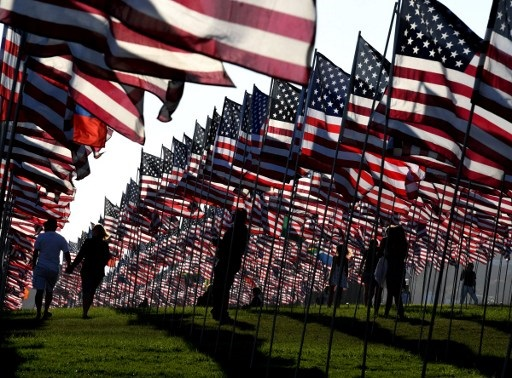 People walk amongst US national flags erected by students and staff from Pepperdine University as they pay their respects to honor the victims of the September 11, 2001 attacks in New York, at their campus in Malibu, California on September 10, 2016.  The students placed aound 3,000 flags in the ground in tribute to the nearly 3,000 victims lost in the attacks almost 15 years ago.  AFP PHOTO