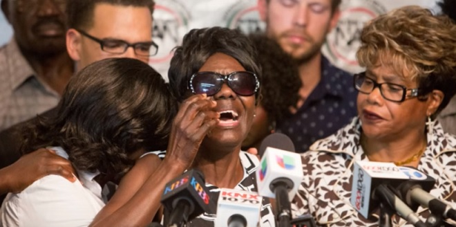 Olango's Mum reacts at a press briefing.