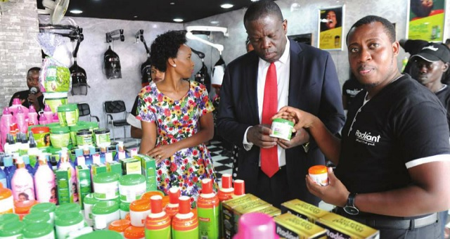 Minister of State for Trade, Michael Werikhe Kafabusa, (M) checks out some of the Radiant products at the 24th UMA Uganda International Trade Fair on Oct. 5. Looking on is the brand ambassador Barbie Kyagulanyi, (L) and Ibrahim Karemera,(R) the Radiant PR manager. INDEPENDENT/JIMMY