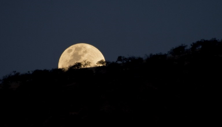 """An unusually large and bright Moon -the closest """"supermoon"""" to Earth in 68 years- adorns the night sky in Santiago on November 13, 2016. / AFP PHOTO / MARTIN BERNETTI"""