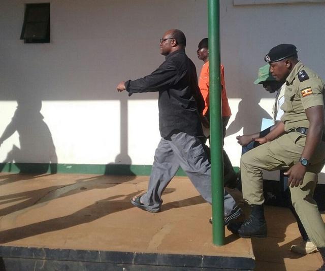 Mumbere being led to court. PHOTO @943qfmlira