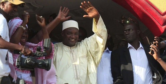 This video grab taken from footage shot by AFPTV shows The Gambia's President-elect Adama Barrow (C) gesturing to the crowd in Kololi on December 2, 2016 following his victory in the polls.  The Gambia's President-elect Adama Barrow was to hold talks with his coalition to plot his transition to power, following a shock election victory that ended the 22-year rule of Yahya Jammeh. The scenes of jubilation on the streets after the results were released gave way to a calm but buoyant mood in the capital Banjul as horsetrading got under way behind closed doors.  / AFP PHOTO / AFPTV / Joe Sinclair